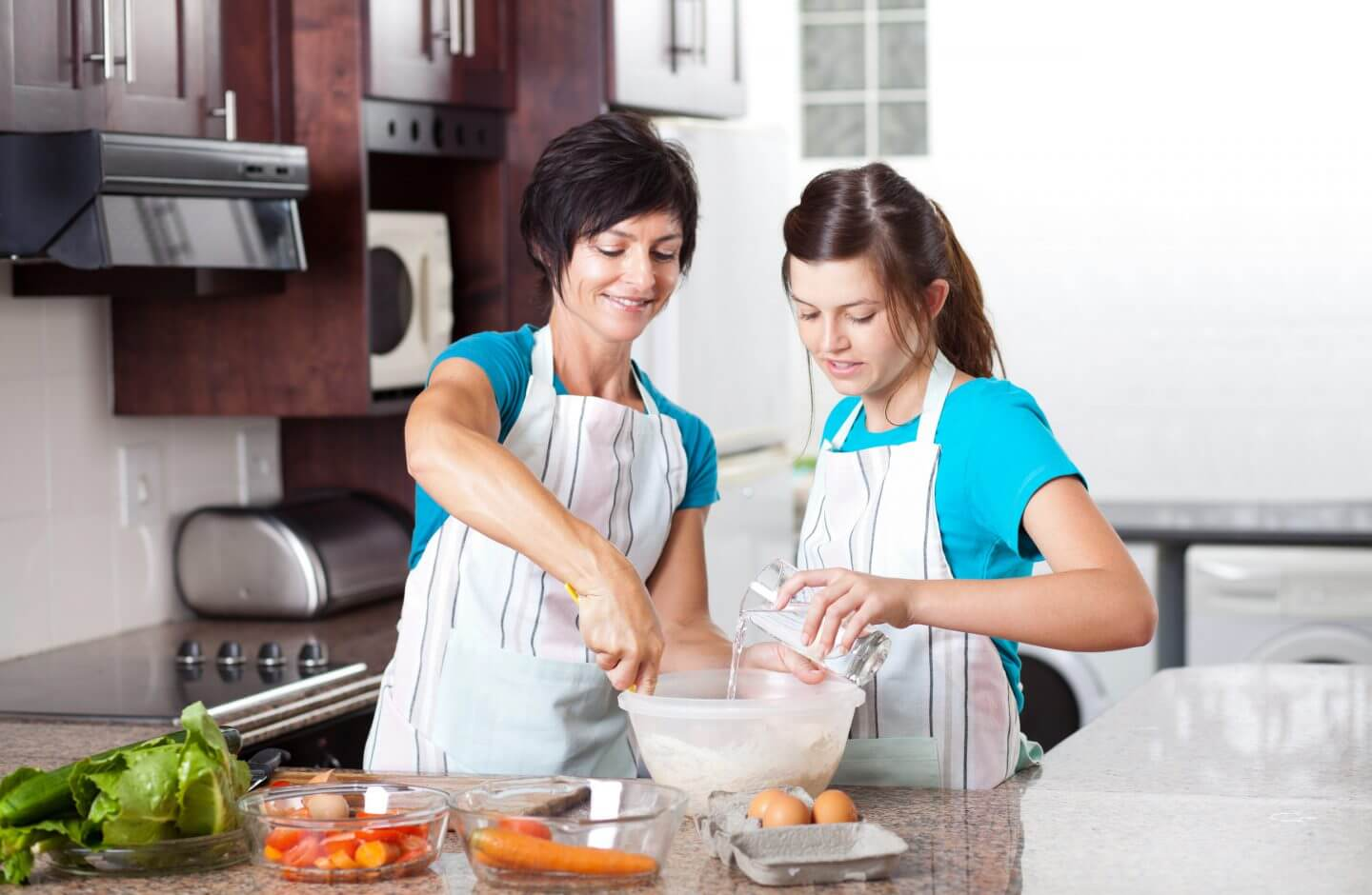 Mother and daughter cooking with cleaner, healthier water from a whole house water filter