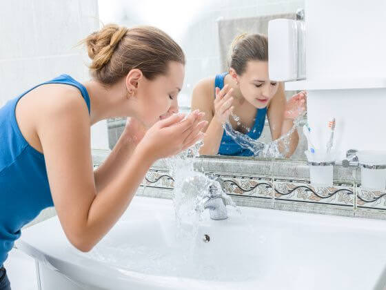 Woman cleaning face with softer, healthier water from a home water softener system