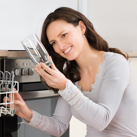 Woman inspecting clean, clear glass from a dishwasher on a water softener system