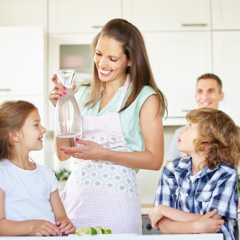 Mom providing cleaner, better-tasting water for her children with a whole house water filtration system