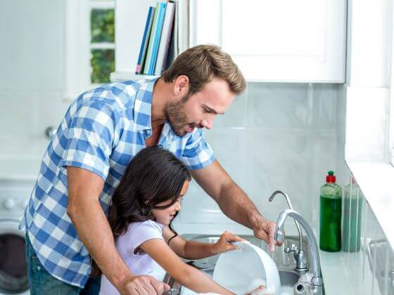 Father and daughter washing dishes with cleaner, healthier water from whole house water filtration system