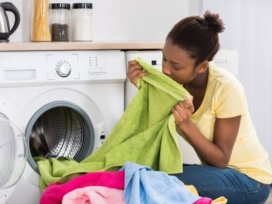 Woman enjoying the smell of cleaner, softer laundry from washing machine on a home water softener system