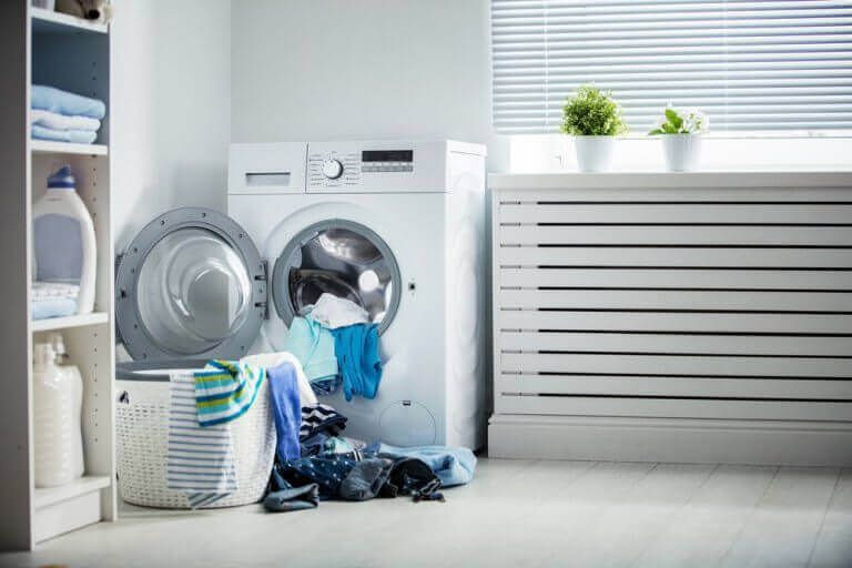 Clean soft clothes halfway unloaded from washing machine on water softener system