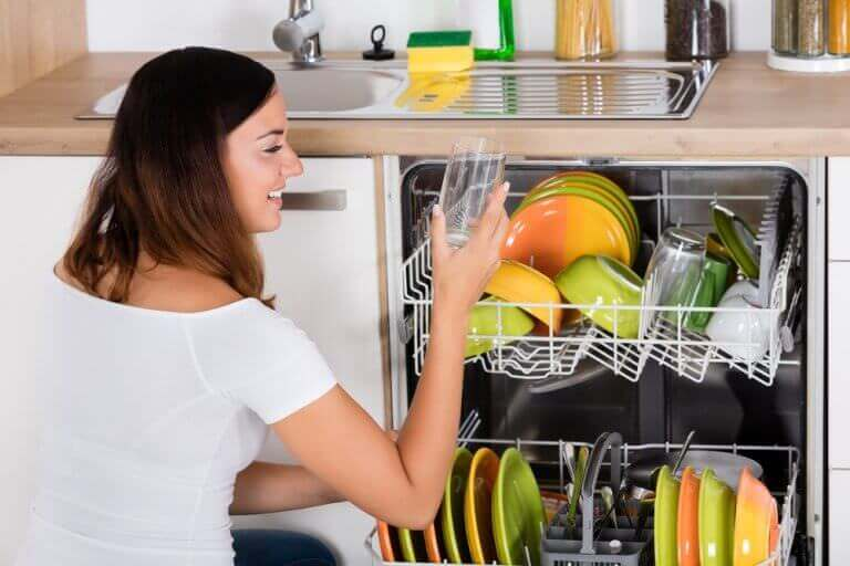 Woman inspects clean and clear glass from dishwasher on a water softener system