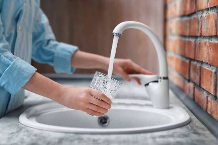 Woman fills glass with clean water from sink connected to whole house water filters