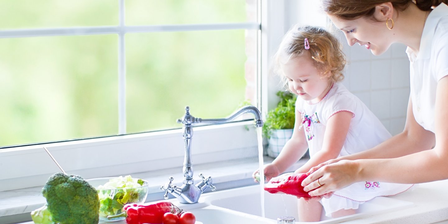 Mother and daughter using sink to wash food using clean and affordable filtered water